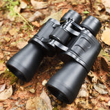 This is a pair of black binoculars that was photographed in the forest