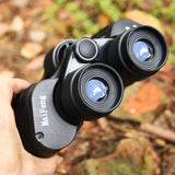 This is a pair of black binoculars that have been photographed in the forest