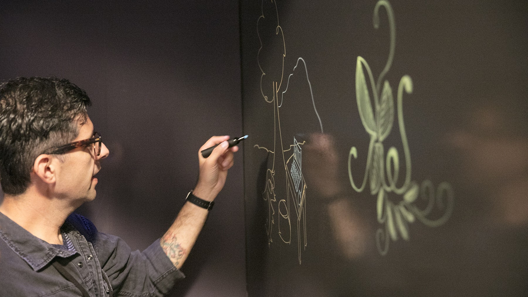 male drawing on a wall painted with Benjamin Moore's Clear High Gloss Notables Dry Erase Paint