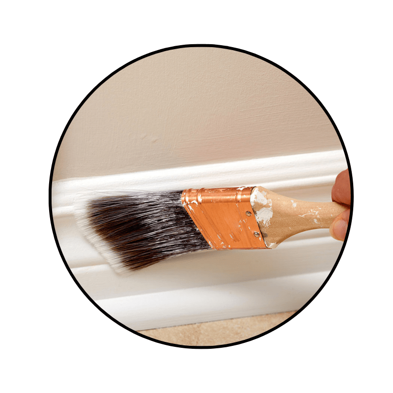 paint brush, brushing white paint onto trim and baseboards in the interior of a home