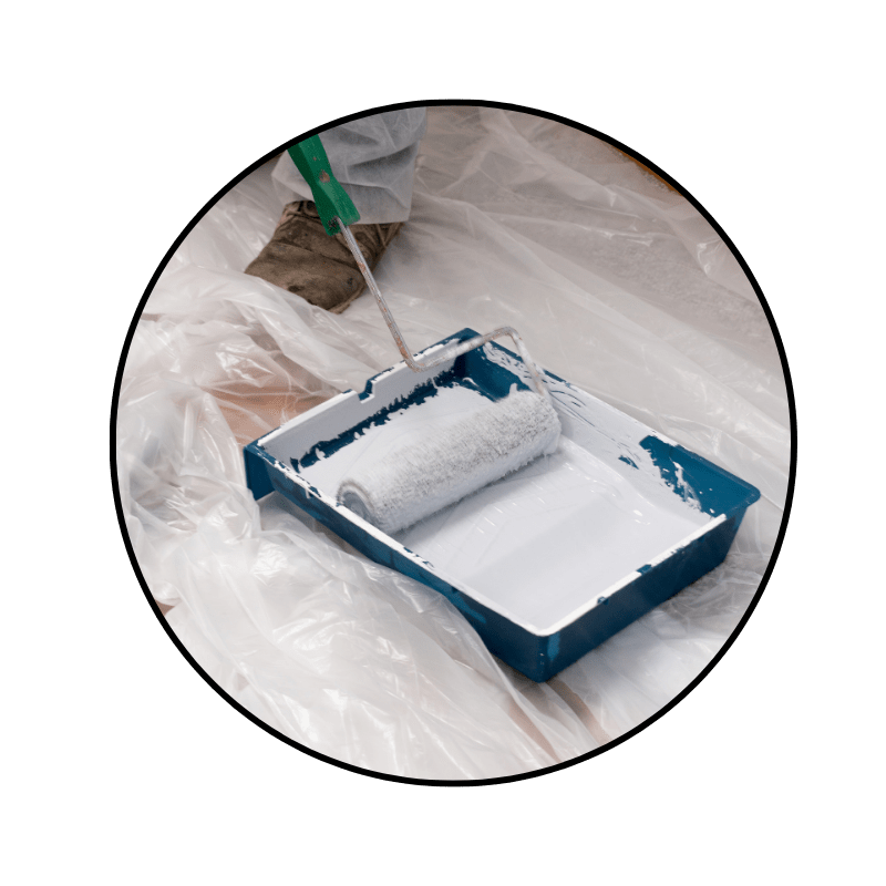 paint roller being dipped into a paint tray and liner on top of a drop cloth