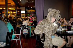 Guy wearing a bear coat in a restaurant with friends.