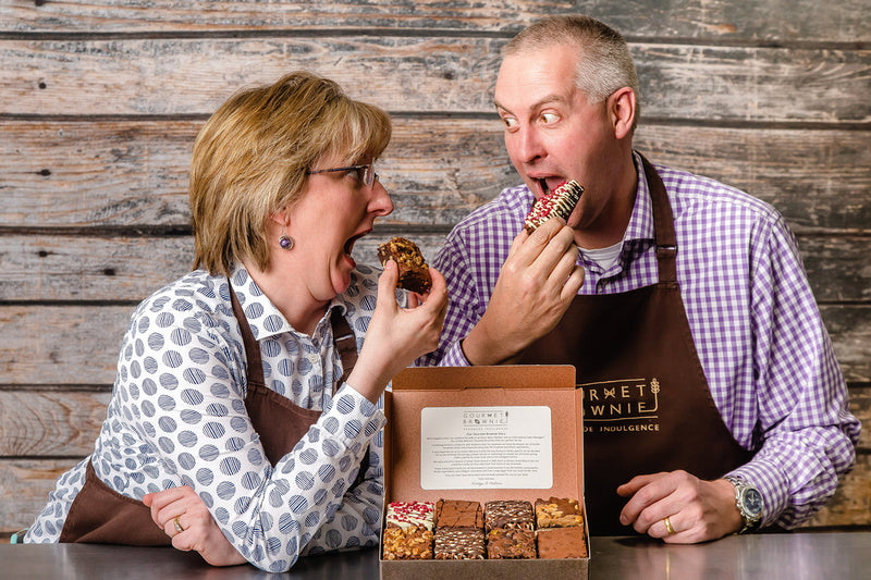 Shows Andrew & Kirstyn Samalionis eating gourmet brownies each pulling a fun, excited face as they draw the brownies to take a bite.  In from of them is a selection box of 8 slices of brownies.