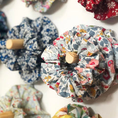 Liberty print scrunchies in different colours hanging on wooden pegs on a wall.