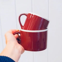 Hand holding red mugs with a cream trim