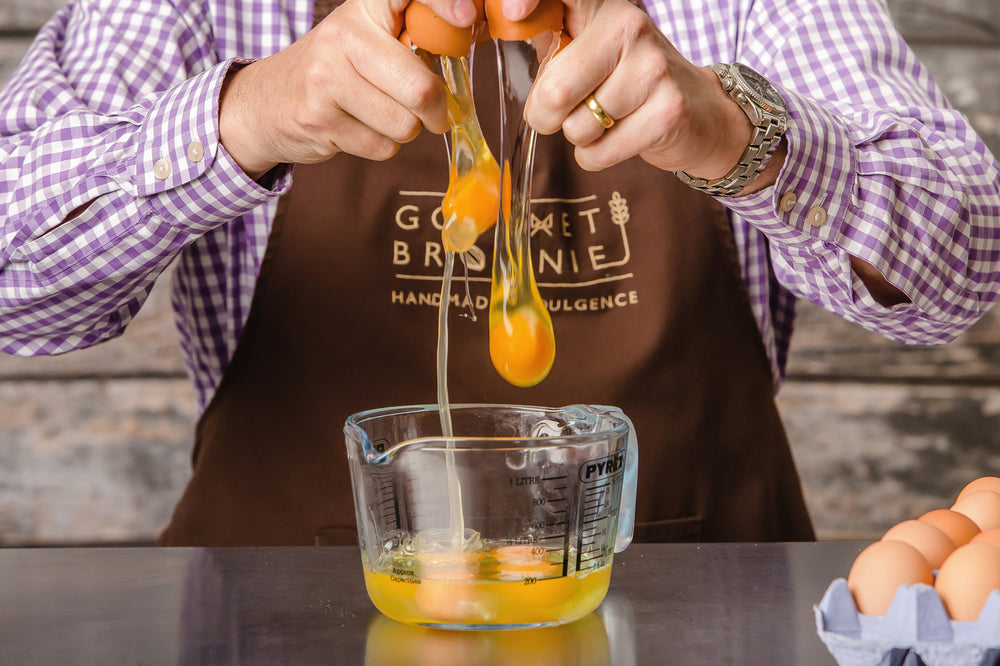 Man cracking 2 eggs into a glass jug.  Jug ready has cracked eggs in.  Man wears a company apron with the gourmet brownie logo showing.  A tray of untracked eggs in the forefront of the picture.