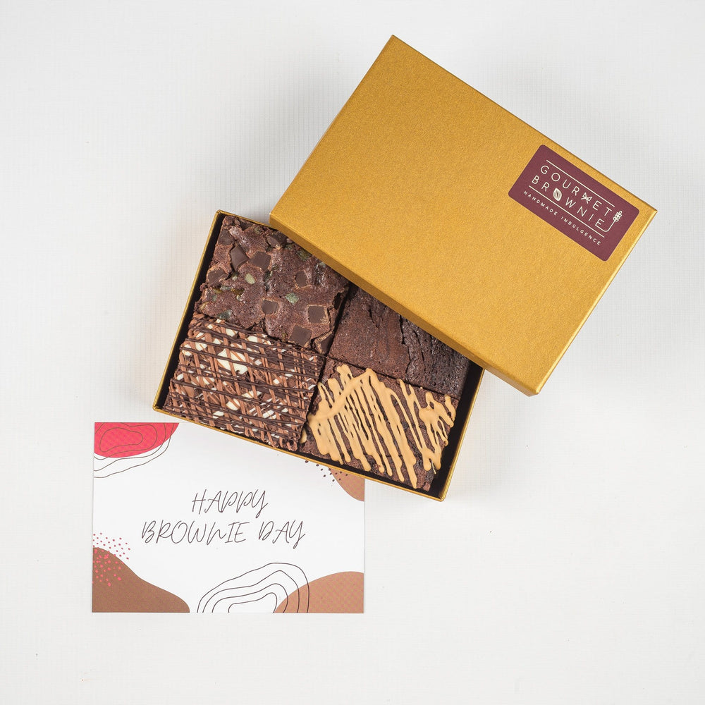 Small chocolate brownie gift box showing four slices of brownie.  Each a different flavour and topped with different ingredients or chocolate drizzle.  'Happy Brownie Day' gift card under box of brownies.