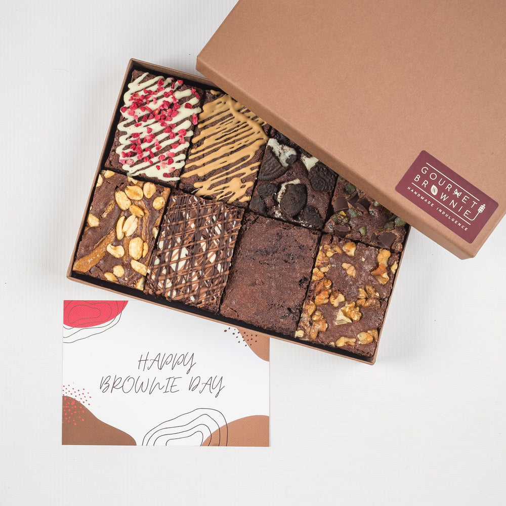 Chocolate brownies shown in a gift box.  All chocolate brownies with different toppings and chocolate drizzles.  Shows a 'Happy Brownie' day gift card.