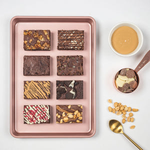 Load image into Gallery viewer, Eight slices of chocolate brownies shown in a baking pan.  Each chocolate brownie has a different topping or chocolate drizzle.  Next to baking pan are baking utensils and dishes holding chocolate.
