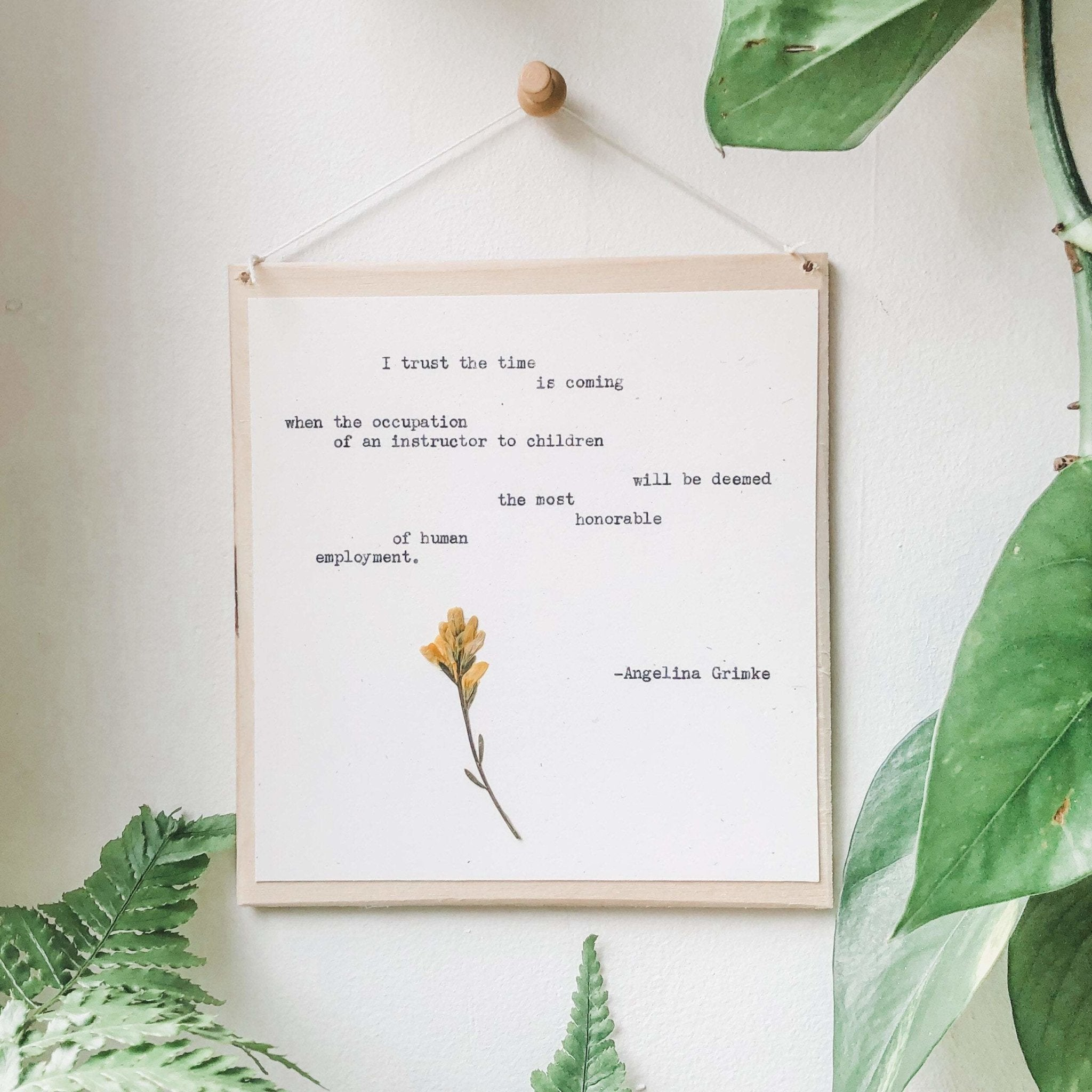 anton chekhov quote typed in typewriter font on white paper, mounted on birch wood and paired with a pressed flower.