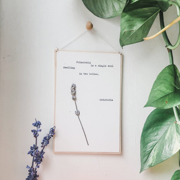 anton chekhov quote typed in typewriter font on white paper, mounted on birch wood and paired with a pressed flower. handmade décor by flora & phrase