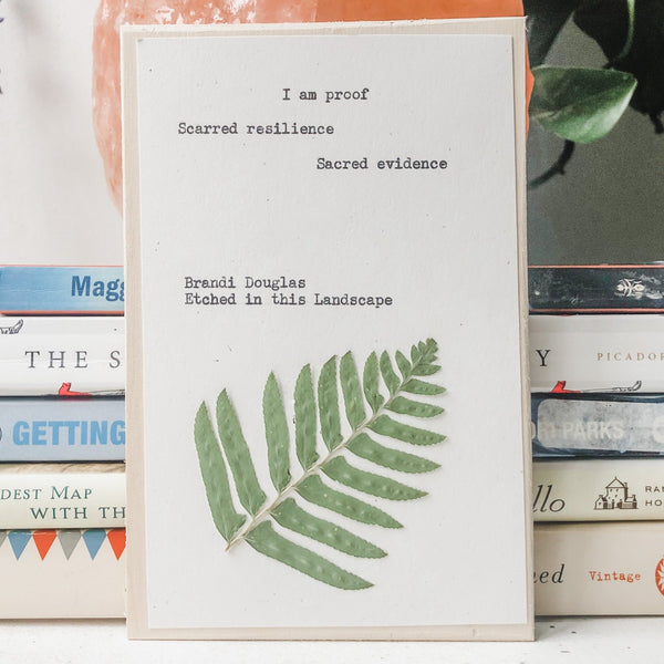 brandi douglas poem typed in typewriter font on white paper, mounted on birch wood and paired with a pressed flower. handmade décor by flora & phrase