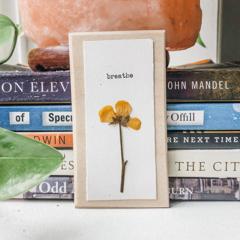 breathe typed in typewriter font on white paper, mounted on birch wood and paired with a pressed flower. handmade décor by flora & phrase