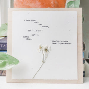 quote from charles dickens, great expectations typed in typewriter font on white paper, mounted on birch wood and paired with a pressed flower. handmade décor by flora & phrase