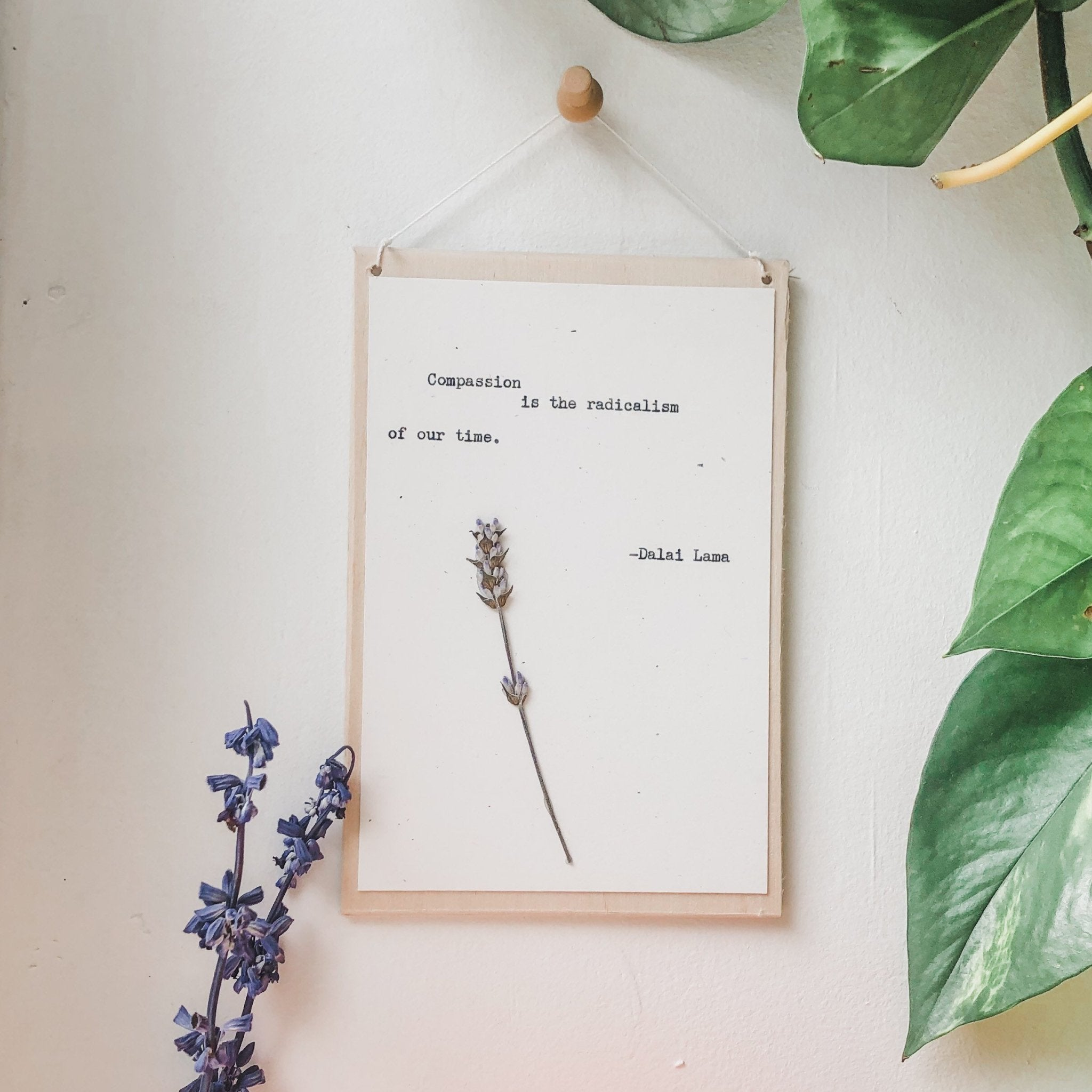 dalai lama, compassion is the radicalism of our time typed in typewriter font on white paper, mounted on birch wood and paired with a pressed flower. handmade décor by flora & phrase