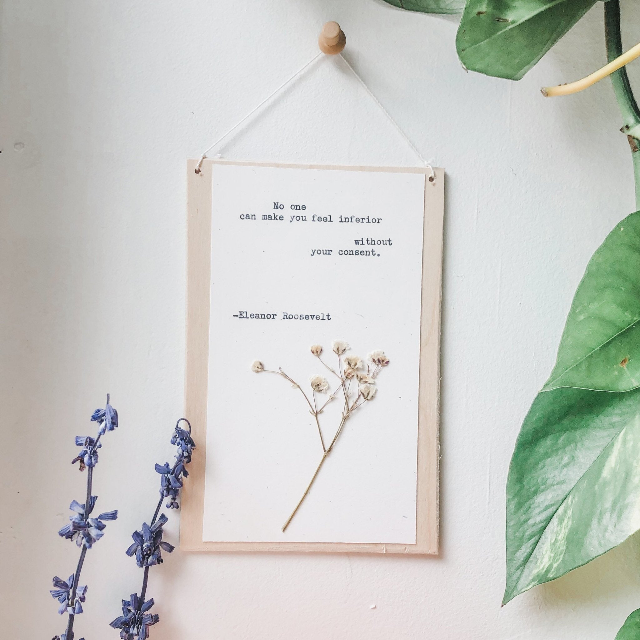 eleanor roosevelt quote typed in typewriter font on white paper, mounted on birch wood and paired with a pressed flower. handmade décor by flora & phrase