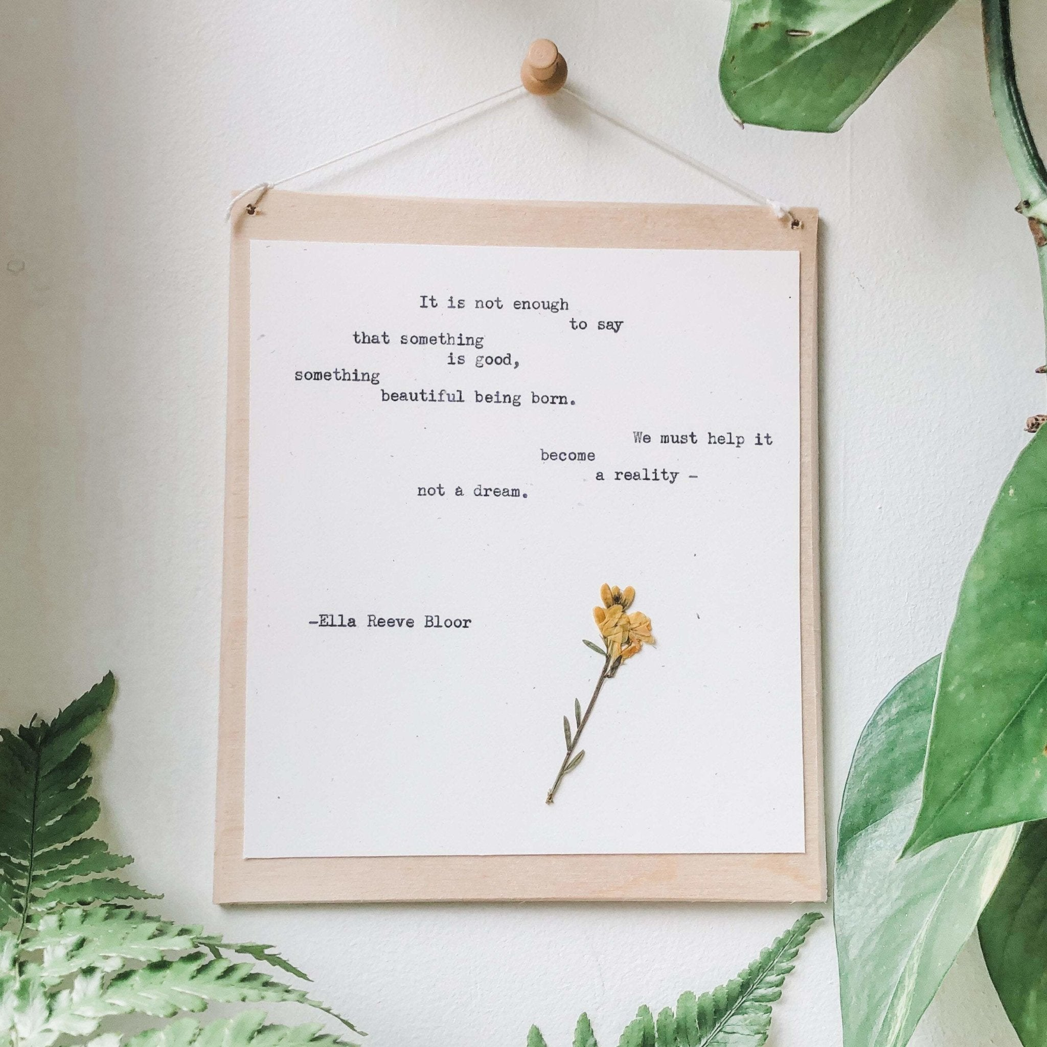 ella reeve bloor quote typed in typewriter font on white paper, mounted on birch wood and paired with a pressed flower. handmade décor by flora & phrase
