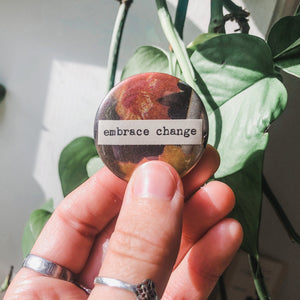 embrace change typed in typewriter font on a colorful background, 1.5 inch pinback button