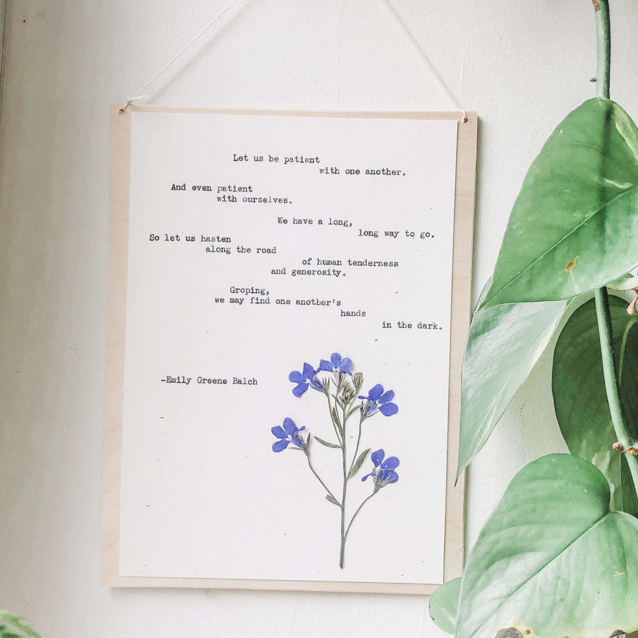 emily greene balch quote typed in typewriter font on white paper, mounted on birch wood and paired with a pressed flower. handmade décor by flora & phrase