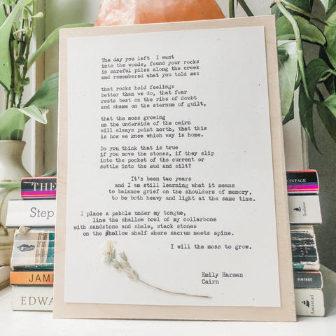 poem by emily harman, cairn typed in typewriter font on white paper, mounted on birch wood and paired with a pressed flower. handmade décor by flora & phrase