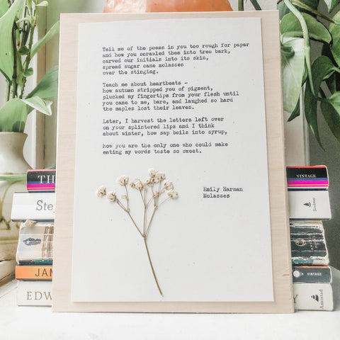 poem by emily harman, molasses typed in typewriter font on white paper, mounted on birch wood and paired with a pressed flower. handmade décor by flora & phrase