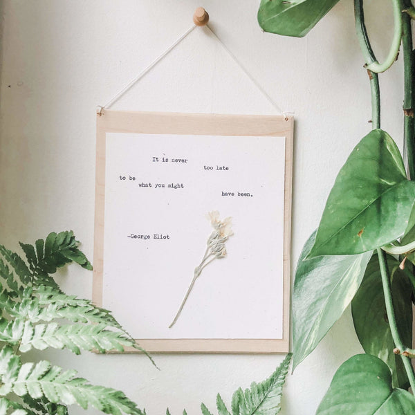 george eliot, it is never too late to be what you might have been quote typed in typewriter font on white paper, mounted on birch wood and paired with a pressed flower. handmade décor by flora & phrase