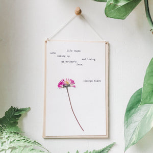 george eliot, loving my mother's face quote typed in typewriter font on white paper, mounted on birch wood and paired with a pressed flower. handmade décor by flora & phrase