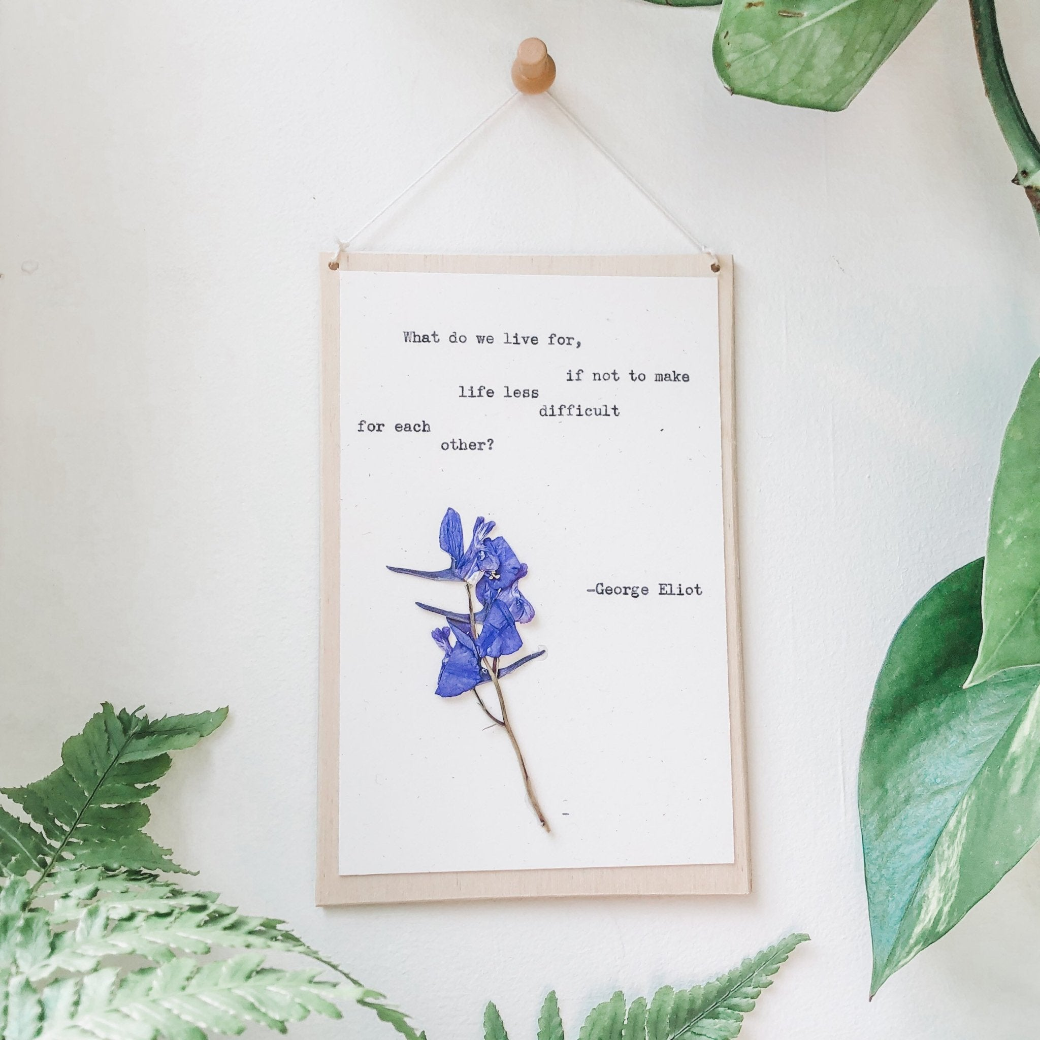 george eliot, make life less difficult for each other quote typed in typewriter font on white paper, mounted on birch wood and paired with a pressed flower. handmade décor by flora & phrase