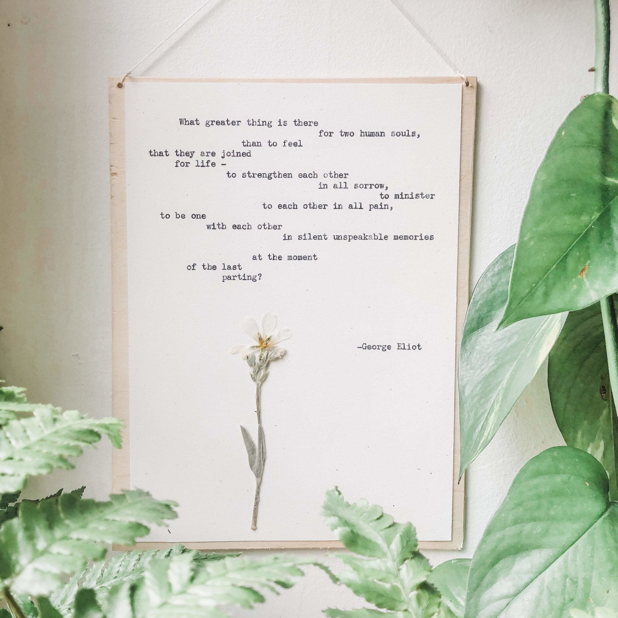 george eliot, two human souls quote typed in typewriter font on white paper, mounted on birch wood and paired with a pressed flower. handmade décor by flora & phrase