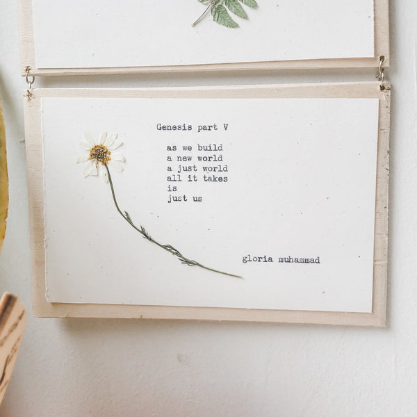 gloria muhammad, genesis I - V poem typed in typewriter font on white paper, mounted on birch wood and paired with a pressed flower. handmade décor by flora & phrase