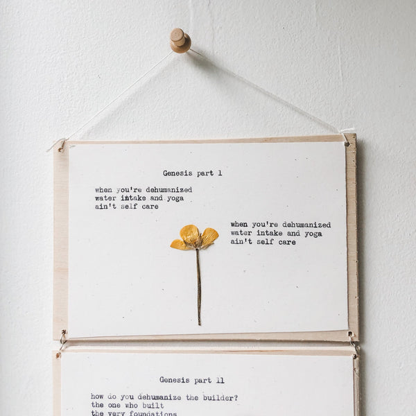 gloria muhammad poem typed in typewriter font on white paper, mounted on birch wood and paired with a pressed flower. handmade décor by flora & phrase