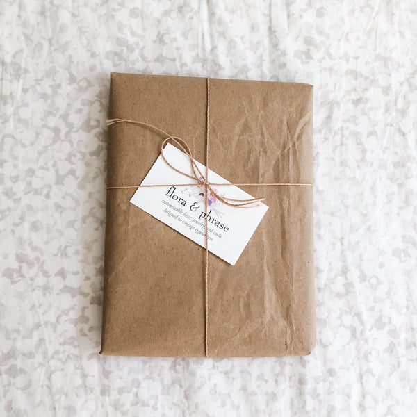 gift wrapped example, kraft paper wrapped in twine and topped with a flora & phrase business card.