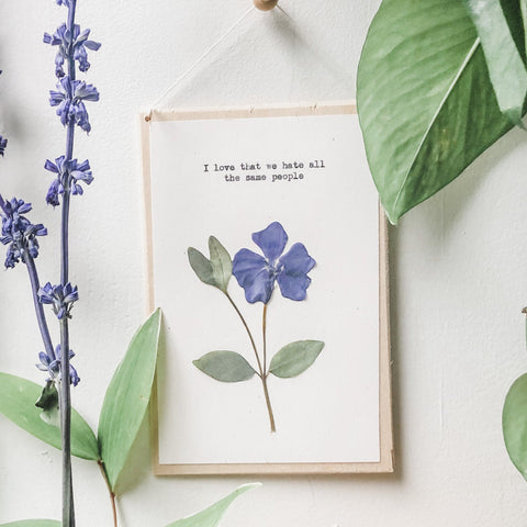 I love that we hate all the same people quote typed in typewriter font on white paper, mounted on birch wood and paired with a pressed flower. handmade décor by flora & phrase