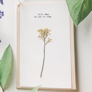 it's okay to not be okay quote typed in typewriter font on white paper, mounted on birch wood and paired with a pressed flower. handmade décor by flora & phrase