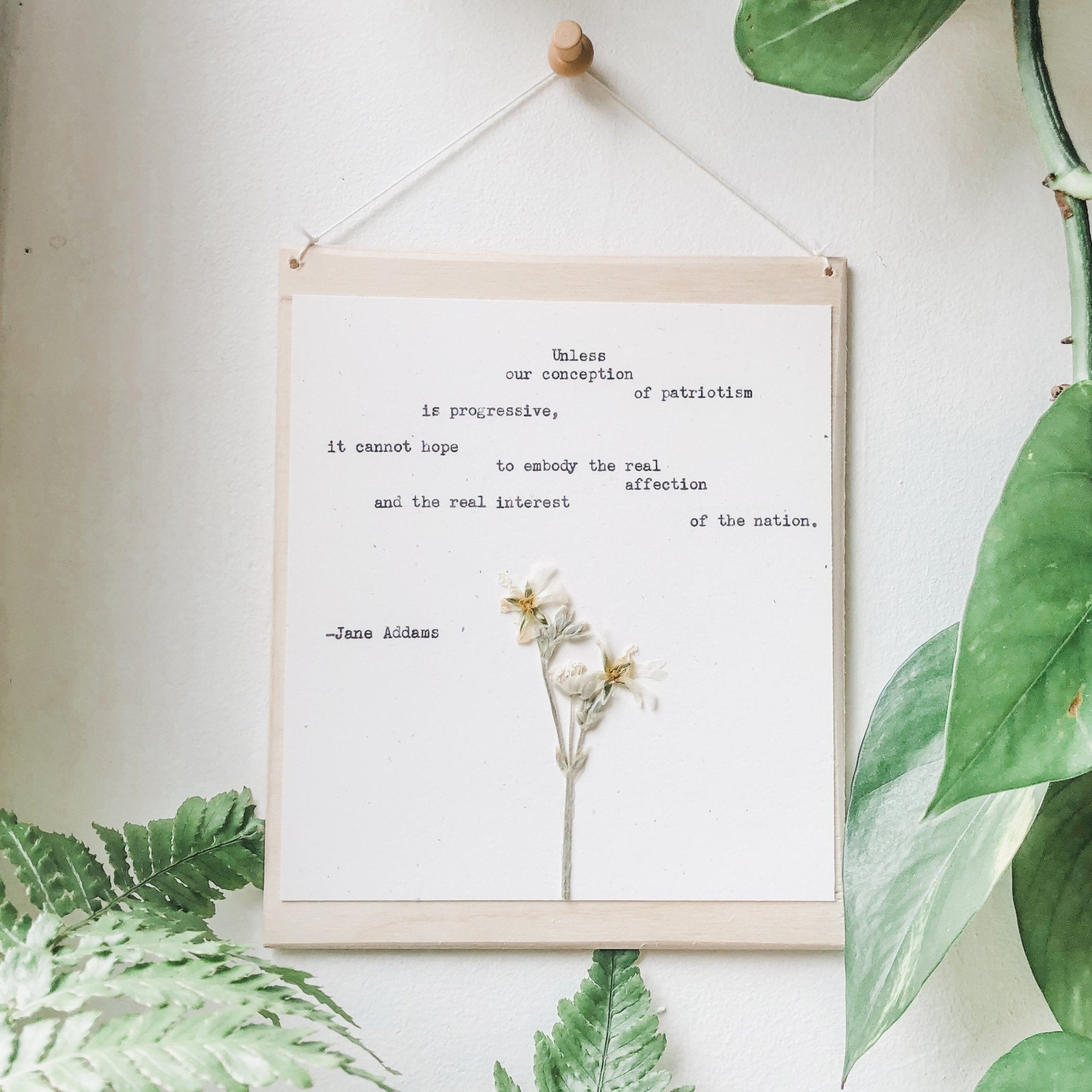 jane addams, progressive patriotism quote typed in typewriter font on white paper, mounted on birch wood and paired with a pressed flower. handmade décor by flora & phrase