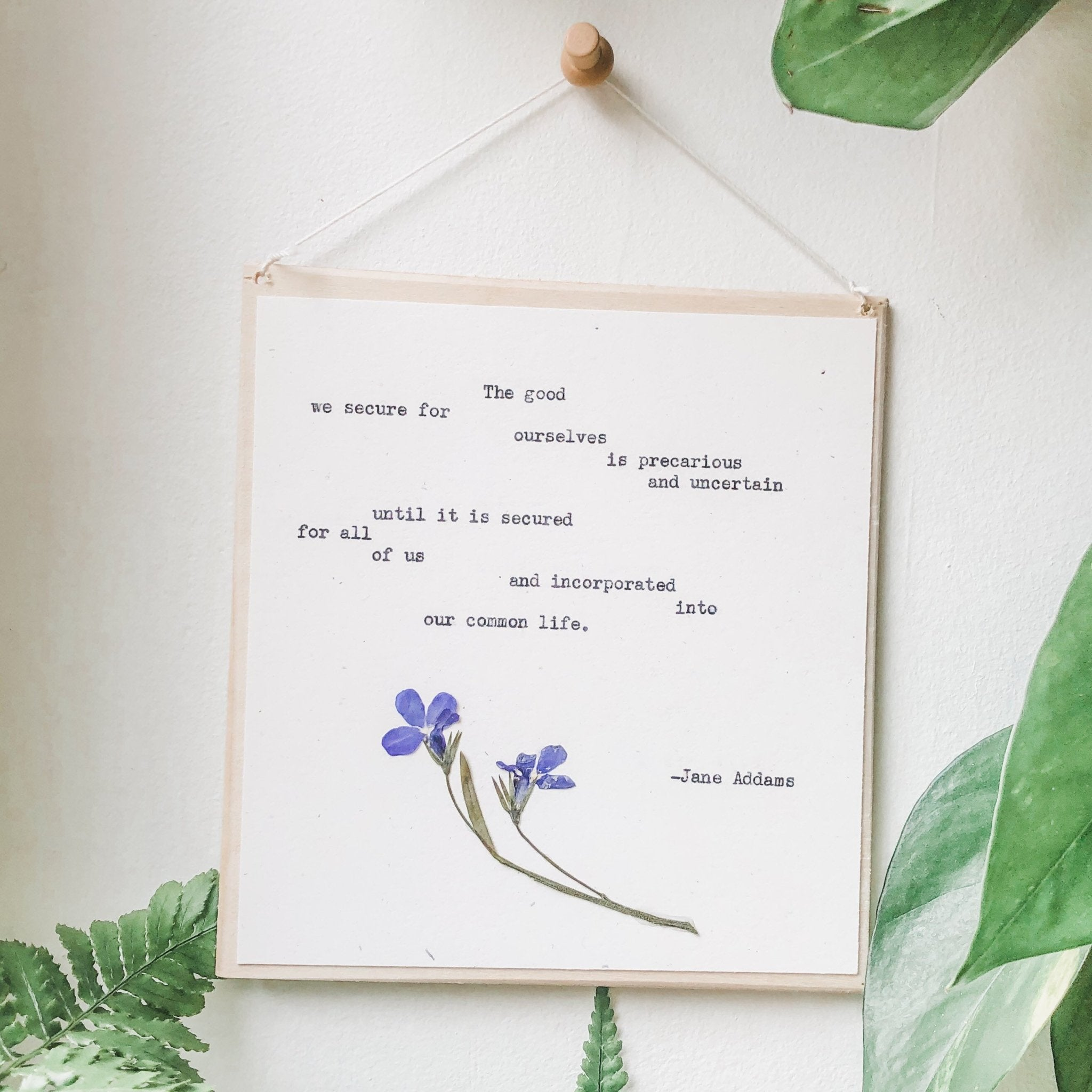 jane addams, the good we secure for ourselves quote typed in typewriter font on white paper, mounted on birch wood and paired with a pressed flower. handmade décor by flora & phrase