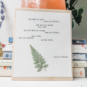 j.r.r. tolkien, not all who wander are lost quote typed in typewriter font on white paper, mounted on birch wood and paired with a pressed flower. handmade décor by flora & phrase