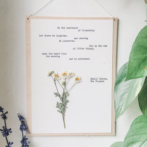 khalil gibran, in the sweetness of friendship quote typed in typewriter font on white paper, mounted on birch wood and paired with a pressed flower. handmade décor by flora & phrase