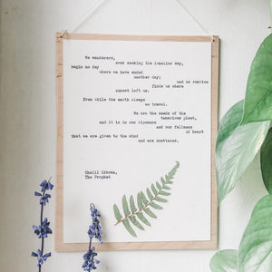 khalil gibran, we wanderers quote typed in typewriter font on white paper, mounted on birch wood and paired with a pressed flower. handmade décor by flora & phrase