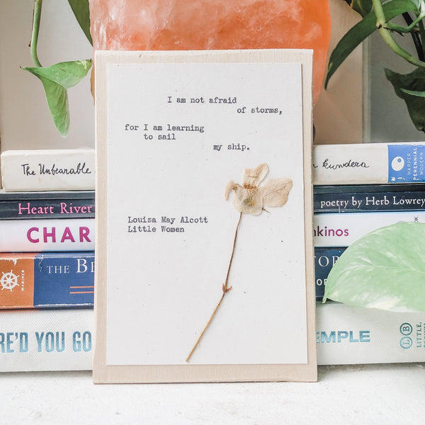 louisa may alcott, I am not afraid of storms for I am learning to sail my ship  quote typed in typewriter font on white paper, mounted on birch wood and paired with a pressed flower. handmade décor by flora & phrase