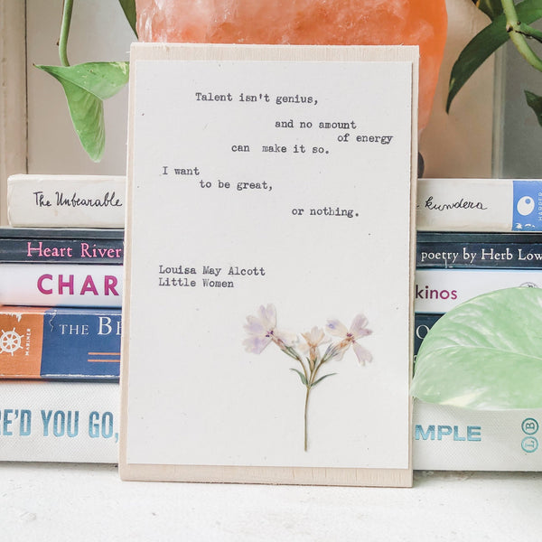 louisa may alcott, I want to be great or nothing  quote typed in typewriter font on white paper, mounted on birch wood and paired with a pressed flower. handmade décor by flora & phrase