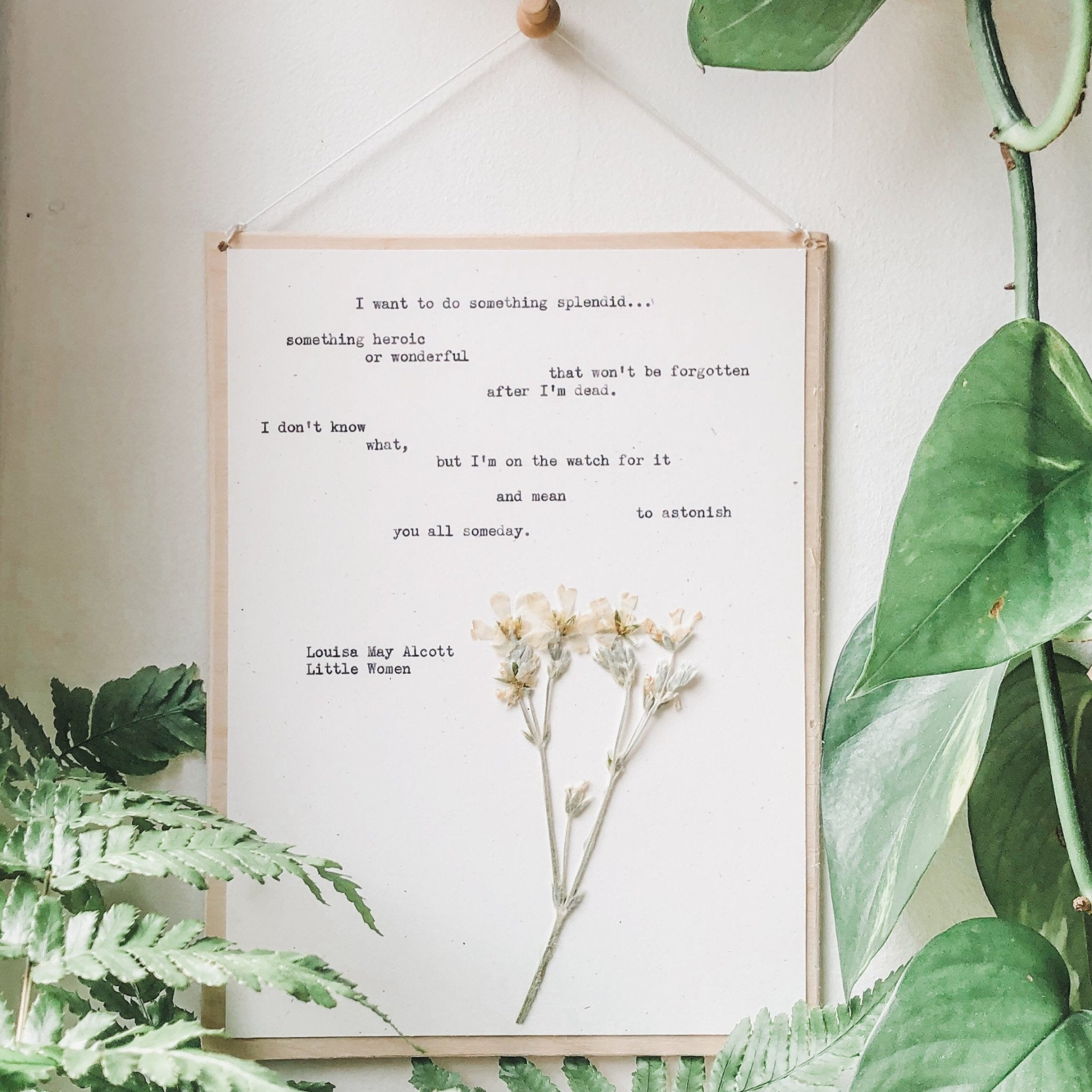 louisa may alcott, I want to do something splendid  quote typed in typewriter font on white paper, mounted on birch wood and paired with a pressed flower. handmade décor by flora & phrase