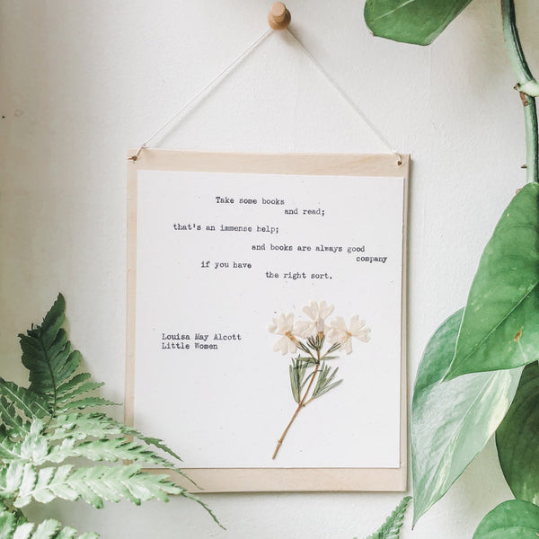 louisa may alcott, take some books and read  quote typed in typewriter font on white paper, mounted on birch wood and paired with a pressed flower. handmade décor by flora & phrase