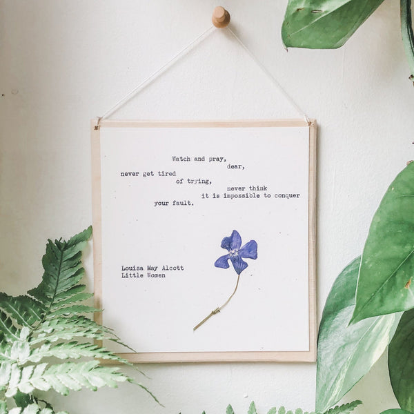 louisa may alcott, watch and pray dear  quote typed in typewriter font on white paper, mounted on birch wood and paired with a pressed flower. handmade décor by flora & phrase