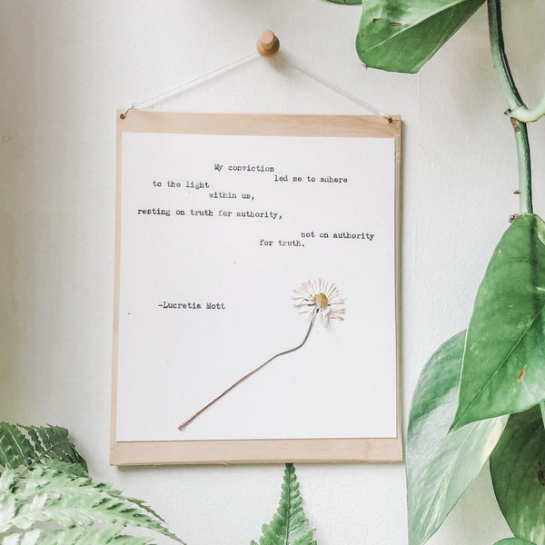 lucretia mott, my conviction  quote typed in typewriter font on white paper, mounted on birch wood and paired with a pressed flower. handmade décor by flora & phrase