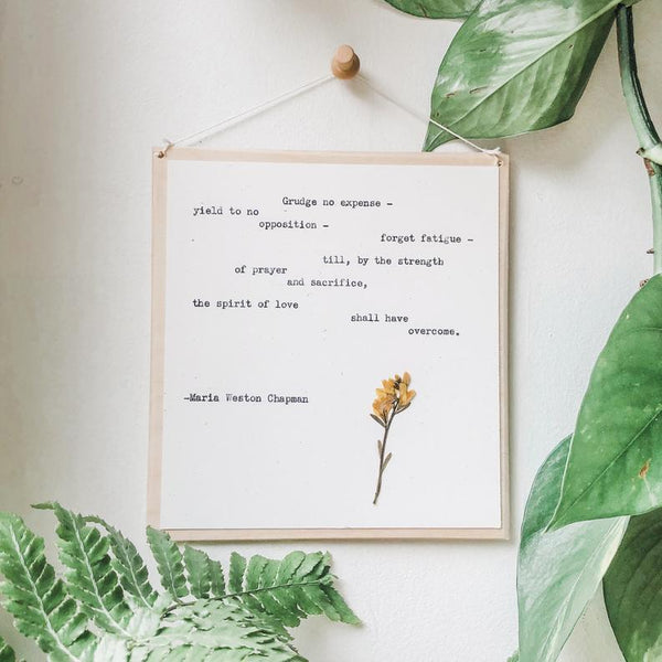 maria weston chapman, the spirit of love quote typed in typewriter font on white paper, mounted on birch wood and paired with a pressed flower. handmade décor by flora & phrase