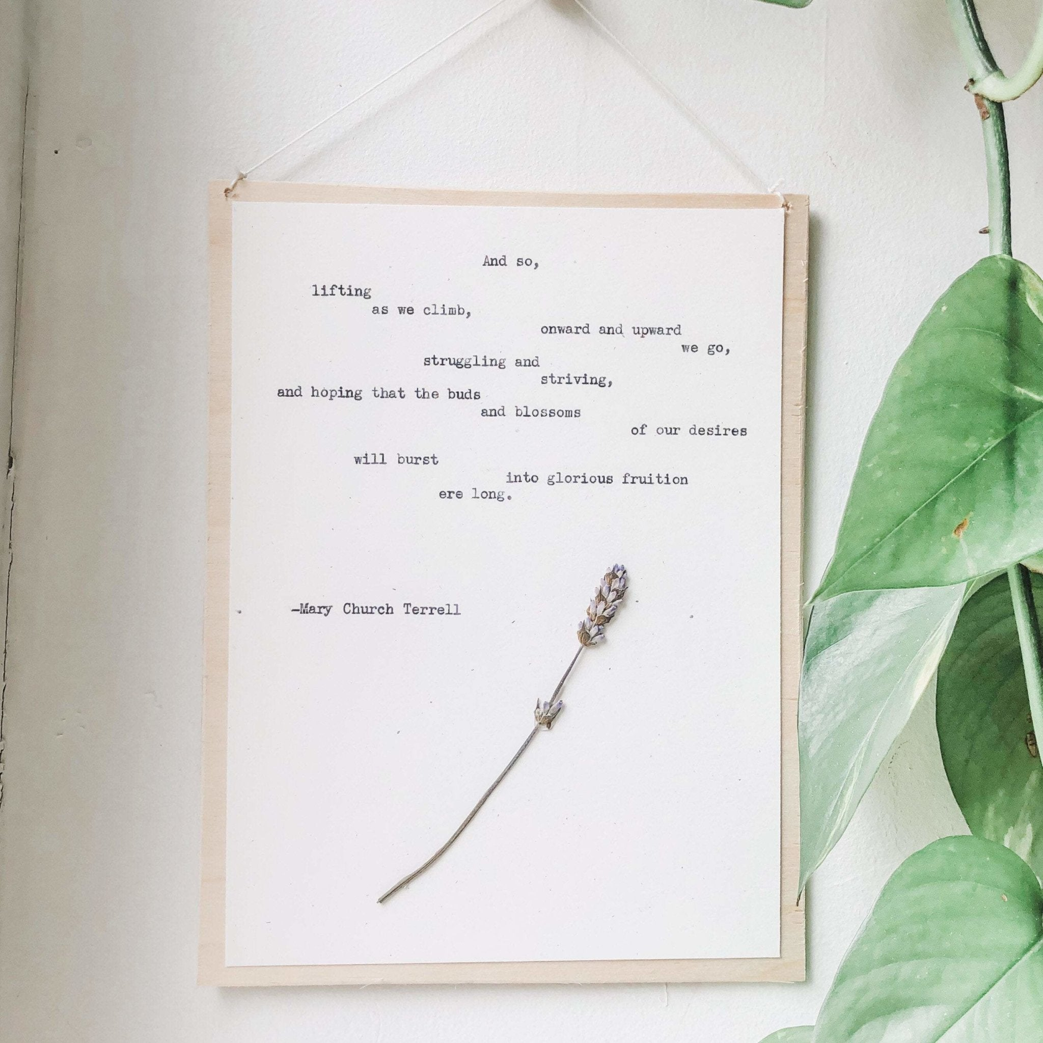 mary church terrell, onward and upward quote typed in typewriter font on white paper, mounted on birch wood and paired with a pressed flower. handmade décor by flora & phrase