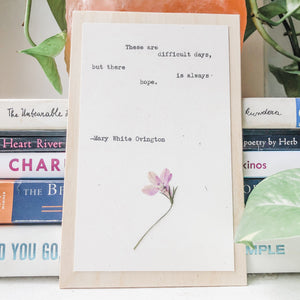 mary white ovington, these are difficult days but there is always hope quote typed in typewriter font on white paper, mounted on birch wood and paired with a pressed flower. handmade décor by flora & phrase