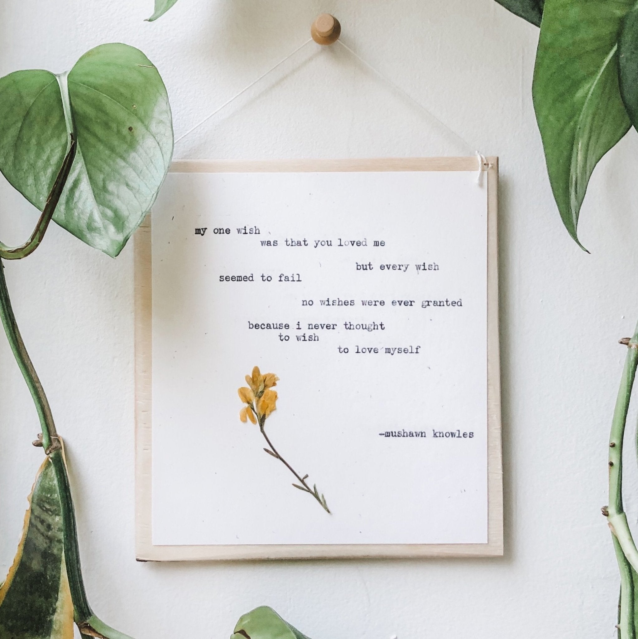 mushawn knowles, my one wish quote typed in typewriter font on white paper, mounted on birch wood and paired with a pressed flower. handmade décor by flora & phrase