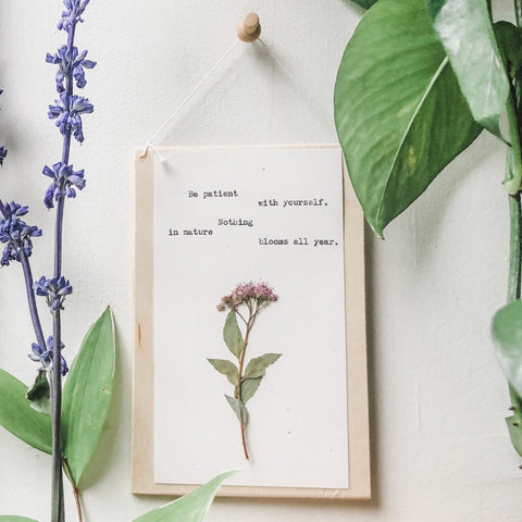 nothing in nature blooms all year quote typed in typewriter font on white paper, mounted on birch wood and paired with a pressed flower. handmade décor by flora & phrase